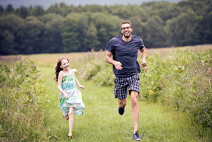 A man and a young child running through a wildflower meadow.の写真素材 [FYI02250373]