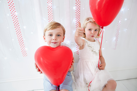 Young boy and girl posing for a picture in a photographers studio, holding red balloons.の写真素材 [FYI02250437]