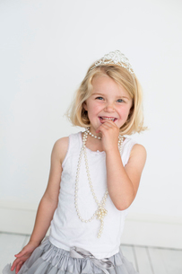 Young girl wearing a tiara and a pearl necklace, posing for a picture in a photographers studio.の写真素材 [FYI02250438]