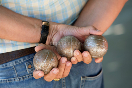 A boules player holding three metal boules in his hands behind his back.の写真素材 [FYI02250440]