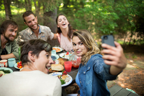 A picnic in woodland. Friends seated around a table, one woman taking a selfy of the group.の写真素材 [FYI02250449]
