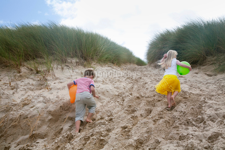 A boy and girl running though soft sand into the sand dunes.の写真素材 [FYI02250497]