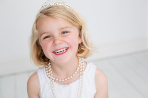 Young girl wearing a tiara and a pearl necklace, posing for a picture in a photographers studio.の写真素材 [FYI02250545]