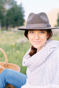 A woman in a hat and woollen shawl sitting in a meadow.の写真素材 [FYI02250549]