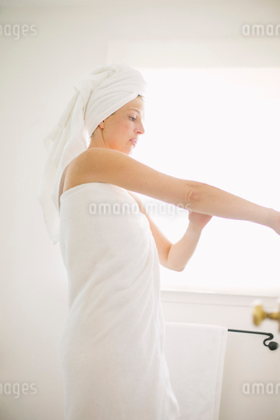 Woman wrapped in a white towel standing in a bathroom, applying lotion to her arm.の写真素材 [FYI02250558]