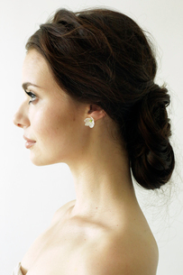 Portrait of a woman with brown hair tied in an elegant bun.の写真素材 [FYI02250563]