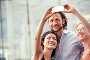 A man and two women on a city street, taking a selfie with a smart phone.の写真素材 [FYI02250565]