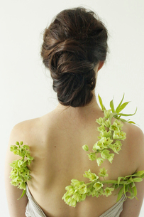 Portrait of a woman with brown hair tied in an elegant bun, wearing a dress with a green flower wreaの写真素材 [FYI02250572]