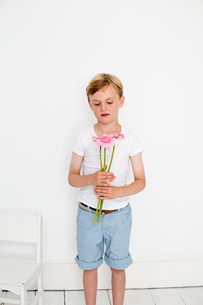 Young boy posing for a picture in a photographers studio, holding a bunch of flowers.の写真素材 [FYI02250573]