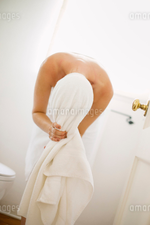 Woman wrapped in a white towel standing in a bathroom, wrapping her hair in a towel.の写真素材 [FYI02250588]