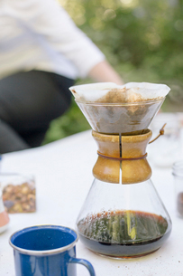Close up of a glass coffee maker on a table in a garden.の写真素材 [FYI02250593]