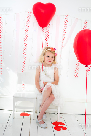 Young girl posing for a picture in a photographers studio, surrounded by red balloons.の写真素材 [FYI02250610]