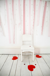 Empty chair in a photographers studio, fairy lights and red streamers on the wall, heart-shaped papeの写真素材 [FYI02250625]