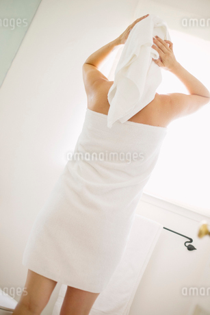 Woman wrapped in a white towel standing in a bathroom, wrapping her hair in a towel.の写真素材 [FYI02250638]