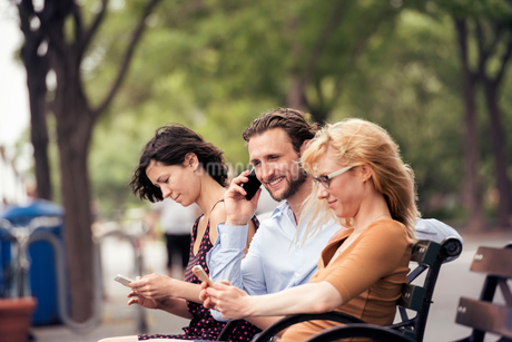 A man and two women seated on a bench in a park, checking their phones, one making a call.の写真素材 [FYI02250655]
