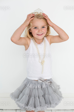 Young girl wearing a tiara and a pearl necklace, posing for a picture in a photographers studio.の写真素材 [FYI02250668]