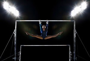 A female gymnast, a young woman performing on the parallel bars performing, with legs extended.の写真素材 [FYI02250670]