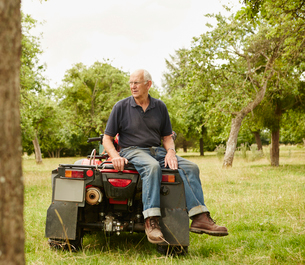 A farmer sitting on the back of a quad bike in a field surveying his land and his animals.の写真素材 [FYI02250676]