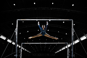 A female gymnast, a young woman performing on the parallel bars performing, with legs extended.の写真素材 [FYI02250703]