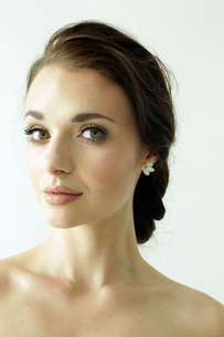 Portrait of a woman with brown hair tied in an elegant bun.の写真素材 [FYI02250705]