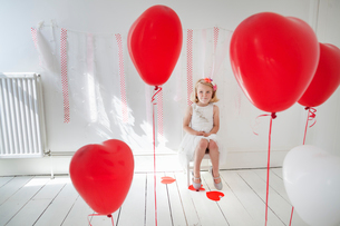 Young girl posing for a picture in a photographers studio, surrounded by red balloons.の写真素材 [FYI02250708]