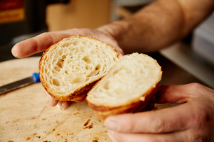 A man holding a croissant cut in half, to show the light layered texture of the cooked dough.の写真素材 [FYI02250717]