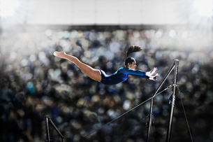 A female gymnast, a young woman performing on the parallel bars, in mid flight reaching towards theの写真素材 [FYI02250721]