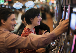 Two people, a young man and woman, playing the slot machines in a casino.の写真素材 [FYI02250736]