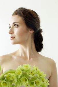 Portrait of a woman with brown hair tied in an elegant bun, wearing a dress with a green flower wreaの写真素材 [FYI02250737]