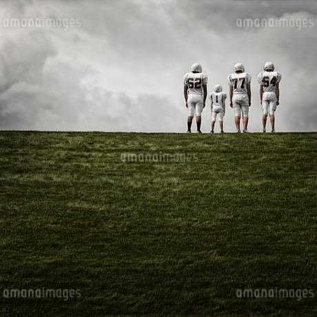A group of four football players in sports uniform, three tall figures and one shorter team player.の写真素材 [FYI02250747]