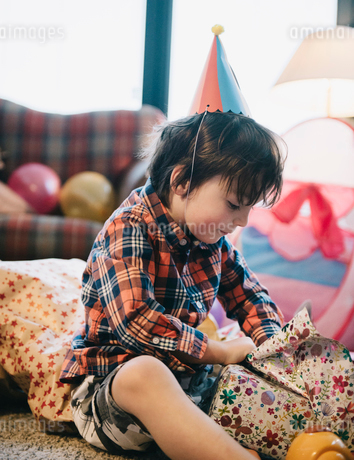A boy unwrapping his presents at his birthday party.の写真素材 [FYI02250764]