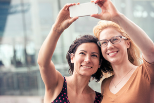 Two women on a city street, taking a selfie with a smart phone.の写真素材 [FYI02250771]