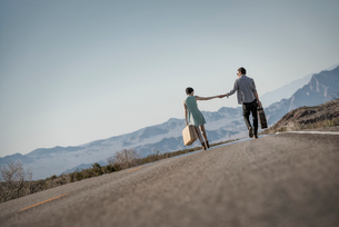 A young couple, man and woman walking hand in hand on a tarmac road in the desert carrying cases.の写真素材 [FYI02250774]