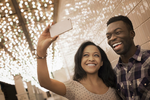 A man and woman in a brightly lit space, a casino entrance, taking a selfy with a smart phone.の写真素材 [FYI02250795]