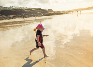 A child in a wetsuit and sunhat running on sandの写真素材 [FYI02250803]