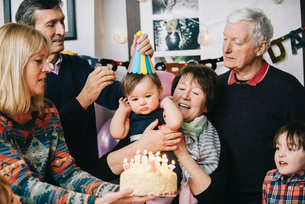 A family gathered to celebrate a one year old girl's birthday party. A cake with lots of candles.の写真素材 [FYI02250822]