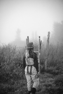 A woman standing on a wooden style in mist.の写真素材 [FYI02250823]