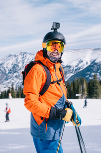 A man in orange ski jacket, with a head cam and helmet.の写真素材 [FYI02250845]