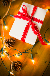 Christmas decorations. Gift box tied with a ribbon and fairy lights.の写真素材 [FYI02250848]