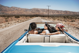 Three young people in a pale blue convertible car, driving on the open road across a flat dry plain,の写真素材 [FYI02250850]