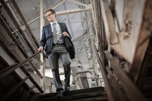 A working day. Businessman in a work suit and tie walking down stairs in a public space.の写真素材 [FYI02250856]