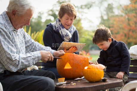 Two adults and a small child with large pumpkins, creating pumpkin lanterns for Halloween.の写真素材 [FYI02250871]