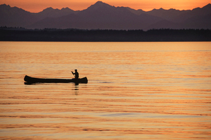 A person seated in a large Indian style canoe paddling across calm water at sunset.の写真素材 [FYI02250874]
