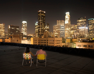 A couple on a rooftop overlooking Los Angeles at night, sitting side by side looking over the city.の写真素材 [FYI02250894]