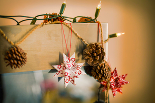 Christmas decorations. Fairy lights, pine cones and paper stars.の写真素材 [FYI02250901]