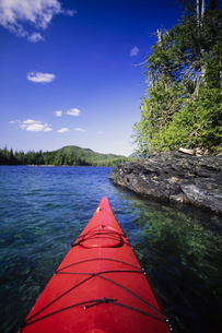 A man in a sea kayak on the clear calm waters off the shore of Ketchikan.の写真素材 [FYI02250910]