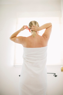 Woman wrapped in a white towel standing in a bathroom, tying her wet hair.の写真素材 [FYI02250919]