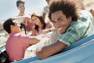 A group of friends in a pale blue convertible on the open road, driving across a dry flat plain surrの写真素材 [FYI02250923]