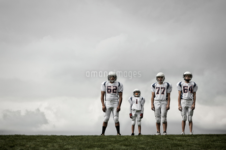 A group of four football players in sports uniform, three tall figures and one shorter team player.の写真素材 [FYI02250926]