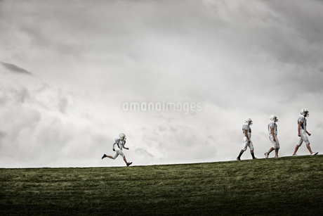 A group of four football players in sports uniform, three tall figures striding along, and one smallの写真素材 [FYI02250940]